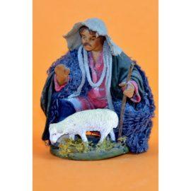 Pastore in ginocchio con pecora