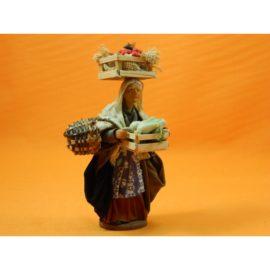 Donna con cassetta di frutta di cera piu' cestino
